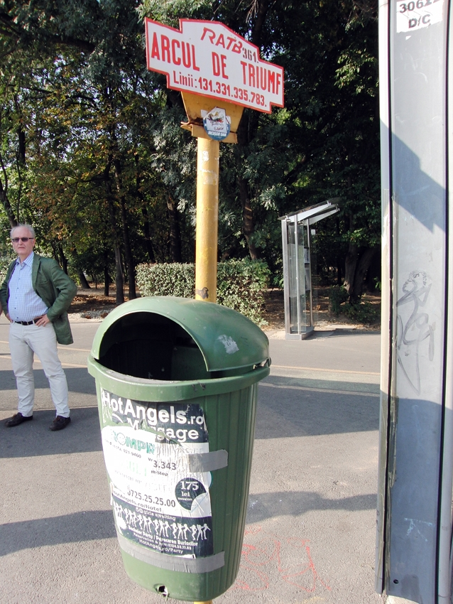 a green litter bin by a sign arcul de triumf in Bucarest Romania