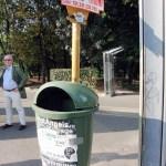 a green litter bin by a sign arcul de triumf in Bucarest Romania