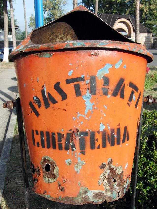 orange litter bin in Curtea de Arges Romania