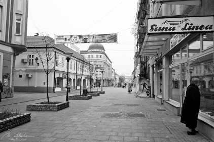 street of Tuzla in black and white with a woman looking through the window of a shop in Bosnia Herzegovina
