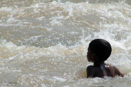 a child is swimming in the Narmada river at Marble Rocks Madhya Pradesh India