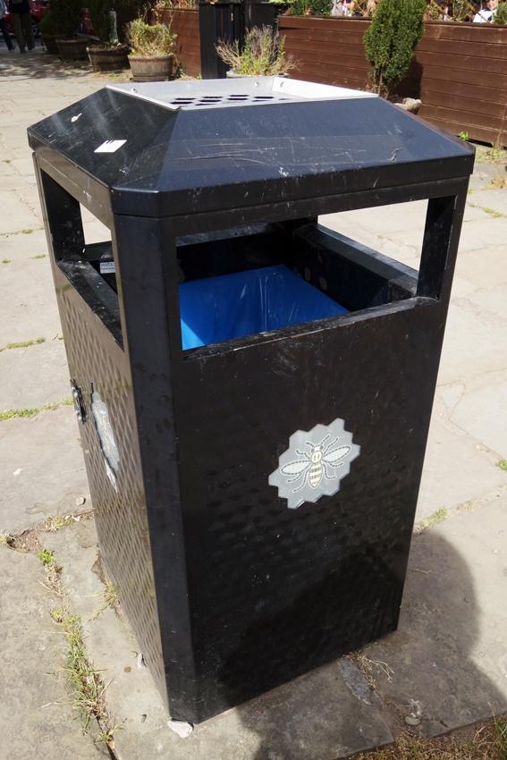 a litter bin in a streef of Manchester with the bee symbol of the city in the United Kingdom
