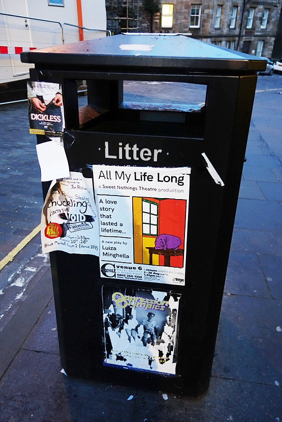 a litter bin in a street of Edinburgh Scotland United Kingdom full of advertisements