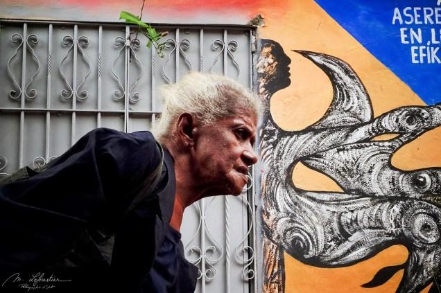 older woman walking in the street callejon de hamel by an art wall in la havana cuba