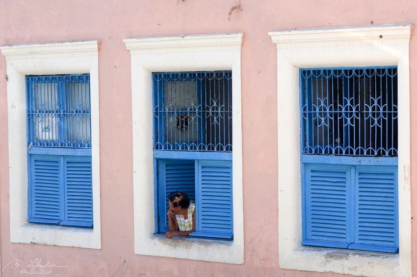 woman watching in the streets from a blue window in Olinda Brazil