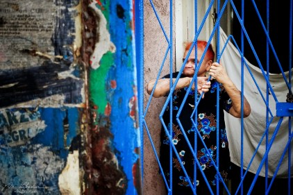 an old woman with red hair watching the street view from inside her house like behind bars in callejon de hamel la havana cuba