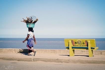 woman carrying a bucket full of bamboo on her head after passing by a yellow bench on the sea front indian ocean in Beira Mozambique