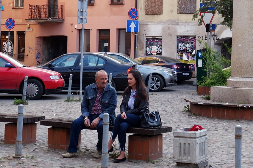 a litter bin in Vilnius Lithuania by parking lot a bench with two people sitting on it