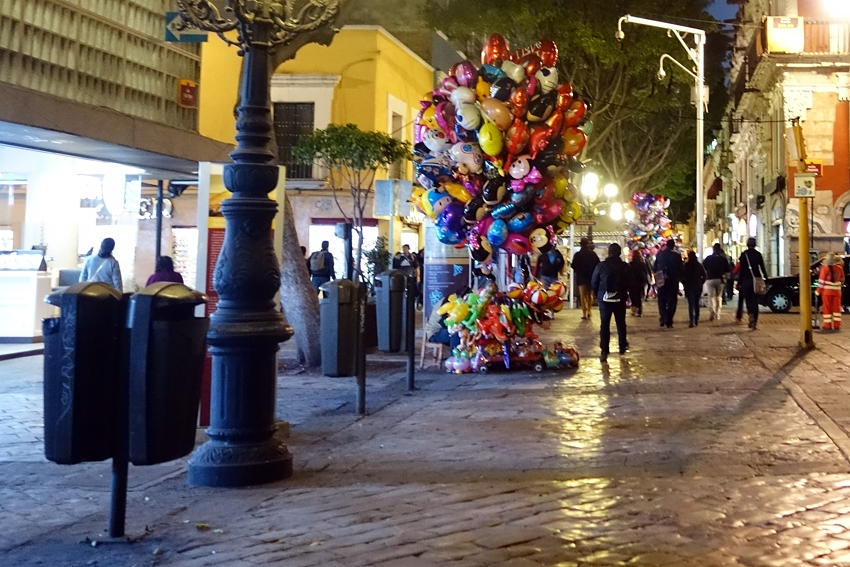 two litter bins in a street in Puebla Mexico by night
