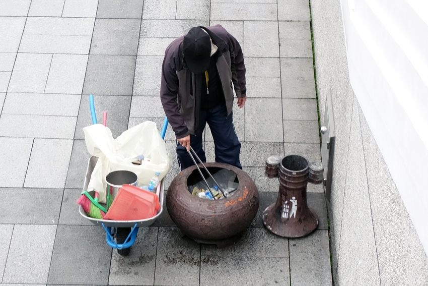 a man picking up trash by a litter bin at the National Palace museum in Taipei Taiwan