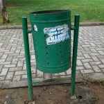 a green litter bin behind the theater of Tirana in Albania