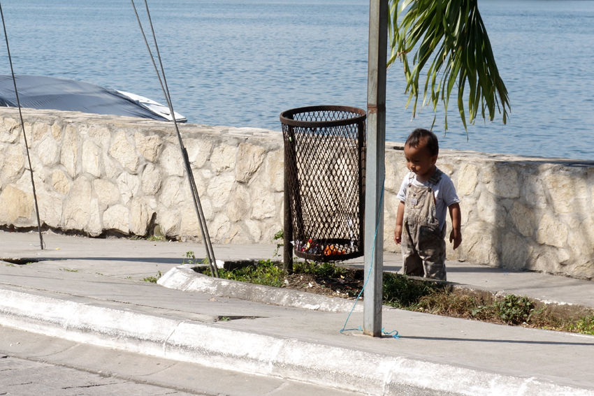 a litter boy looking at a litter bin in Flores Guatemala