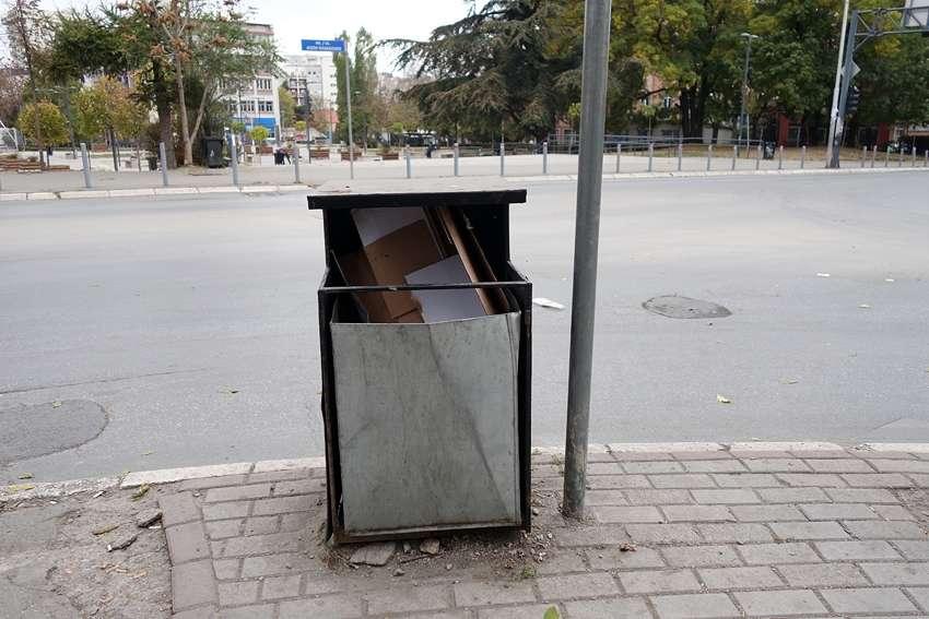 a grey litter bin in a street in Tirana Albania