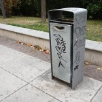 a grey litter bin in a street of Prishtina in Kosovo with tags on it