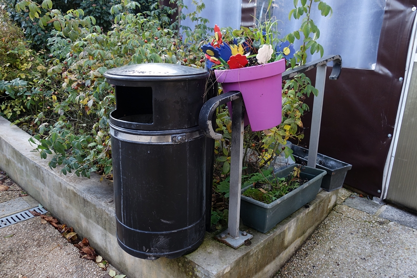 a street litter bin by a pot of fake flowers in the town of Provins France