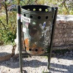an old litter bin, tagged and with stickers in Gjirokaster Albania, a UNESCO world heritage site