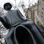 statue of Franz Kafka sitting on a headless figure in a little square on Dusni street in Prague in the Czech Republic