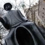 statue of Franz Kafka sitting on a headless figure in a little square on Dusni street in Prague in the Czech Republic