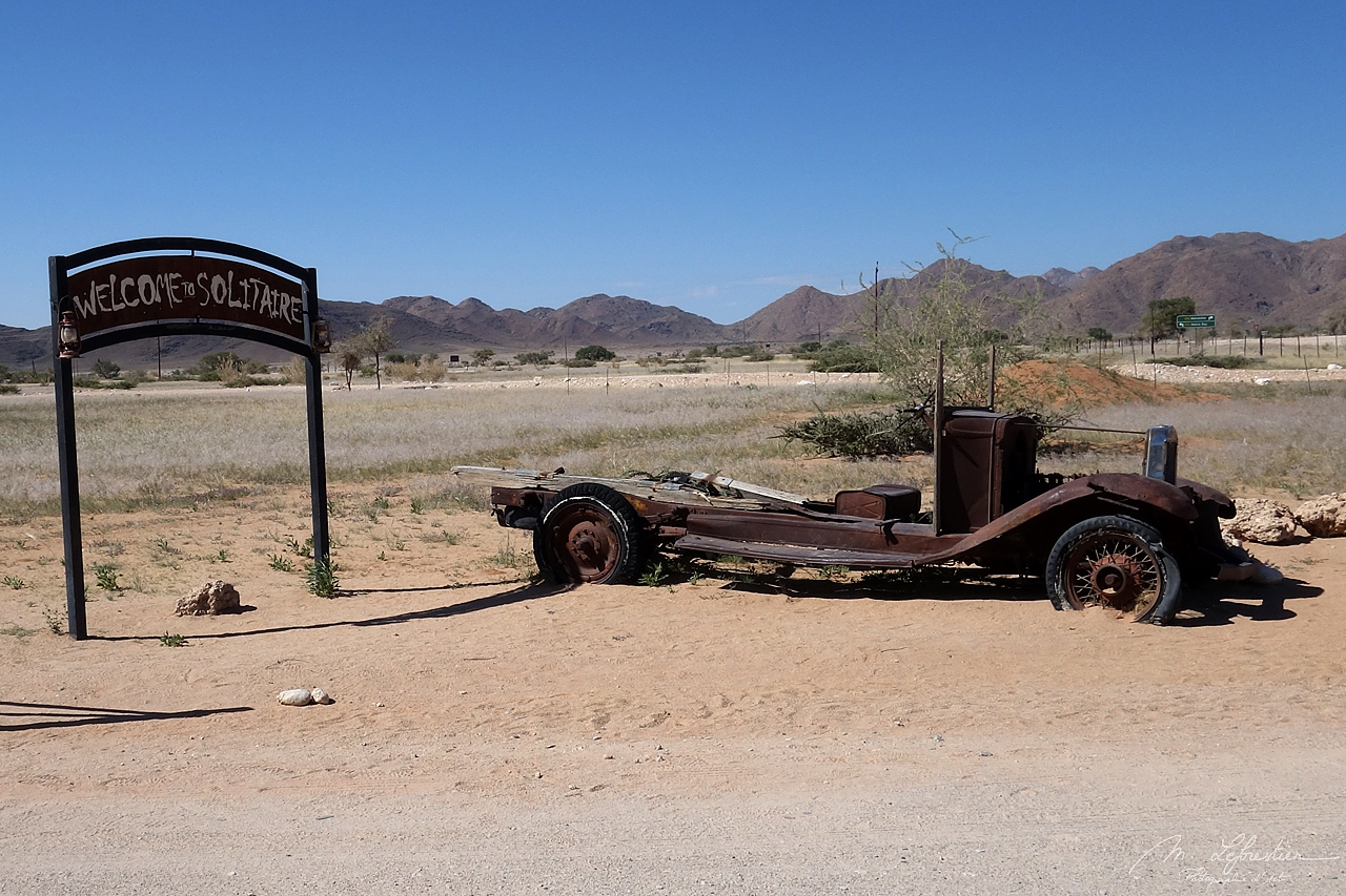 Abandoned car by the Welcome to Solitaire sign in the gas station in the middle of the desert in Namibia