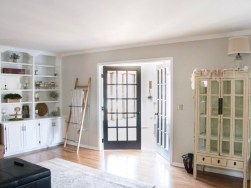 Light wall with white trim and dark doors. Window doors to sunroom