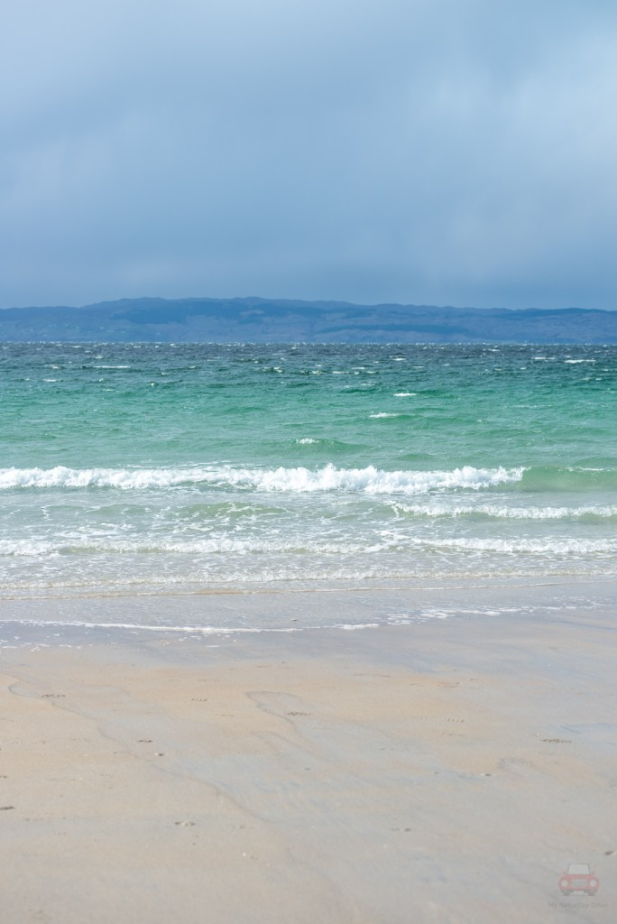 A shot of the stunning turqoise waters of Camusdarach Beach looking towards the Isle of Skye, Scottish Highlands