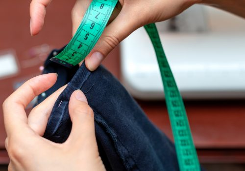 Girl tailor measures a centimeter seam leg.