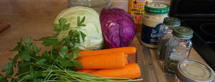 Picture of the ingredients for the colorful coleslaw recipe, all organic, including green and red cabbage, carrots, parsley, mayonnaise, apple cider vinegar and ground up hot pepper.