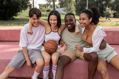 happy multiracial friends embracing on bench after basketball training