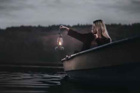 woman on a boat holding gas lantern