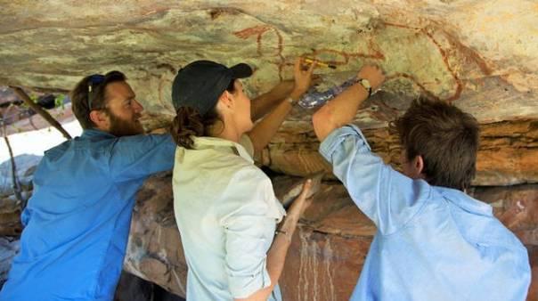 Los investigadores Nick Sundblom, Helen Green y Jordy Grinpukel, remueven diminutas acumulaciones minerales en uno de los paneles con arte rupestre. Kimberley, Australia.