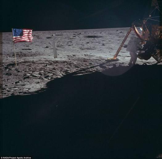 Uno de los astronautas manipula el módulo lunar mientras la bandera estadounidense se muestra tras de él.