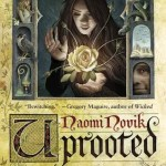 "Cover of ""Uprooted"" by Naomi Novik. Agnieszka is featured in the main, large panel in the upper middle of the cover, holding a yellow rose. An alchemical beaker, a bird, a blonde woman, a three-headed monster, books, and a sword, and the up-close face of a man are shown around her in smaller panels."