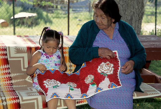 Famille de Native American, une arrière grand mère montre à son arrière petite fille la diversité de dessins utilisés. Ainsi, elle assure la transmission du travail de broderie de perles à la génération suivante. à partir du site suivant: http://viestiphoto.photoshelter.com