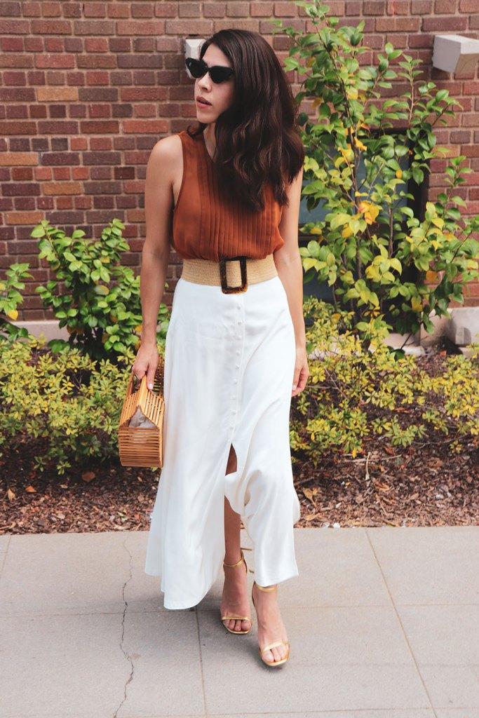 Girl wearing a white skirt wearing a cult Gaia bag