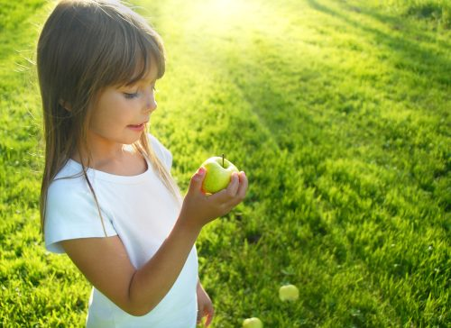 Little,Girl,With,Apple,In,The,Garden