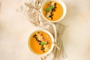 Moroccan spiced carrot soup garnished with dried apricot, feta cheese, pecans, and fresh mint leaf