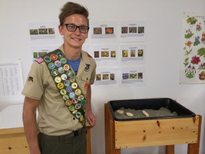 Eagle Scout, Tyler, posing in front of his generous donation of two sensory tables
