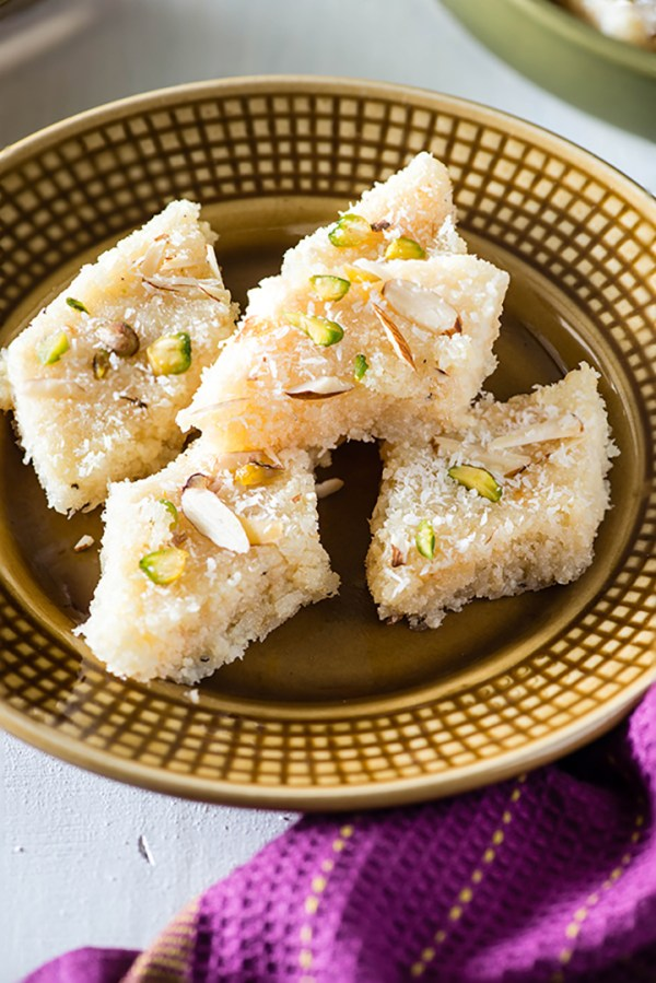 Coconut burfi is tasty traditional Indian sweet that can be made in minutes. Traditionally coconut burfi is made with milk but this is coconut burfi recipe with Milk powder, desiccated coconut, and sugar. An instant Indian Mithai that can be made in minutes.