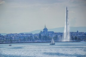 View of Geneva from the lake, with a sailboat and jet d'eau in front