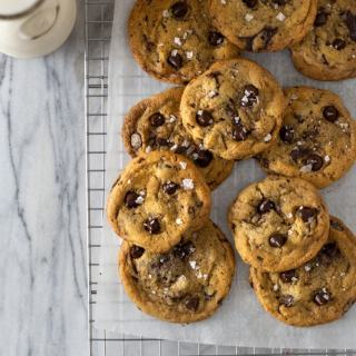 Overhead shot of a group of salted brown butter chocolate chip cookies on parchment paper on a metal wire cooling rack next to chocolate chips and a jug of milk on a marble surface.