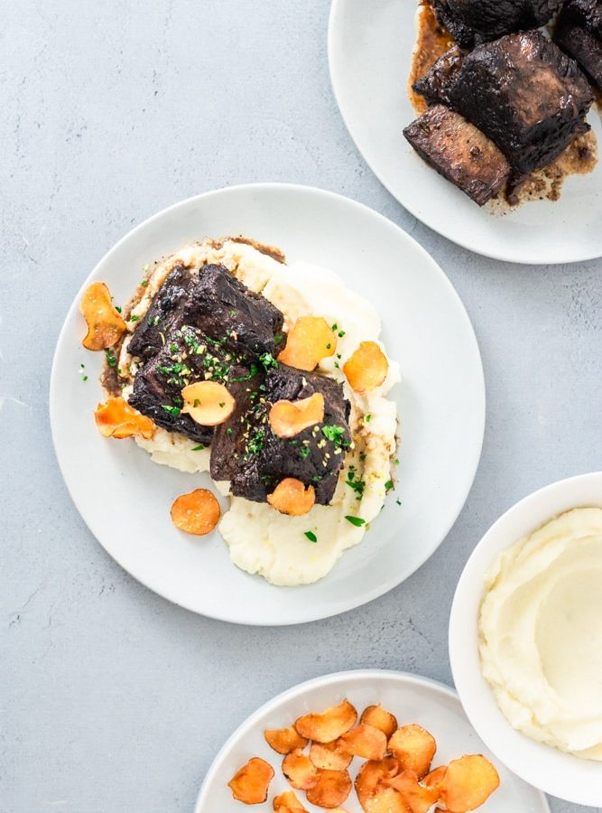 Overhead shot of a plate of Red Wine Braised Short Ribs over sunchoke puree, topped with sunchoke chips, parsley and lemon zest. There are surrounding plates of short ribs, sunchoke puree and chips. The surface is light blue.