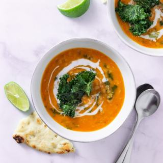 Overhead shot of two bowls of Thai Red Curry Lentil Soup topped with coconut milk and kale chips on a marble surface surrounded by lime wedges, naan bread and spoons.