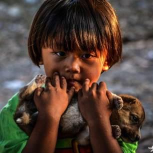 petit thailandais tenant un chiot dans ses mains