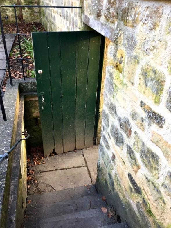 The open invitation door on the way out, aged green with a bit of rot...