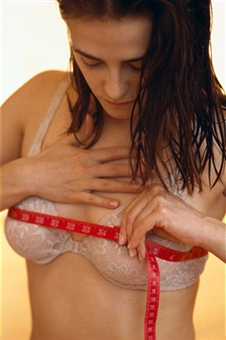 Woman measuring breasts with tape measure