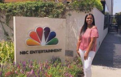 Briana Johnson, USC Marshall School grad, standing next to the NBC Entertainment sign at NBC Universal Studio lot.