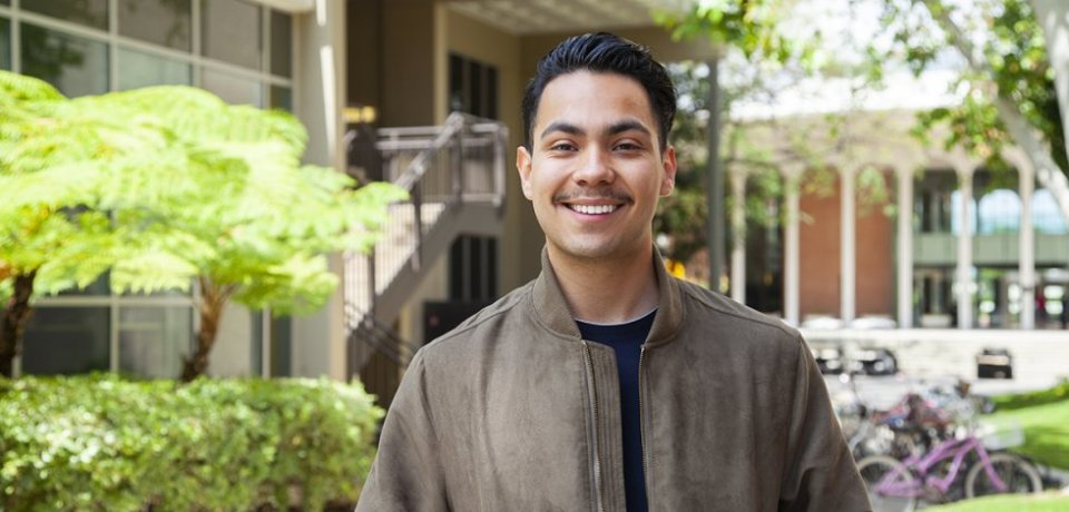 Francisco Jauregui, USC Annenberg senior, photographed standing in front of a building at USC.