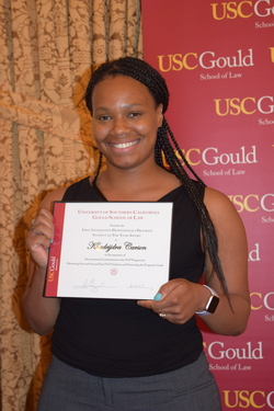USC Gould Law JD, Kiki Carson, photographed holding an award she received, standing in front of a USC Gould School of Law banner.