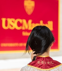 """A photograph of the back of Eugenia Huang, showcasing the stitching on her graduation stole, where it says, """"Her Father's Daughter"""""""