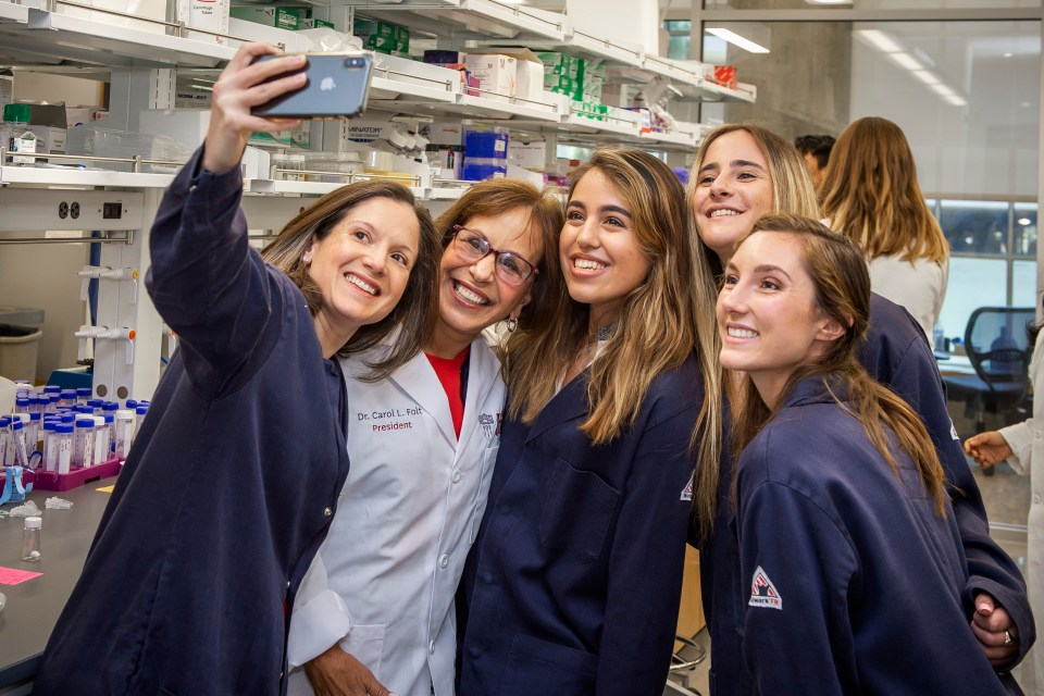 USC President Carol L. Folt is presented with a embroidered lab coat from students and research assistants during her tour of professor Andrea Martin Armani and Professor Eun Ji Chung labs at Michelson Center for Convergent Bioscience, July 16, 2019.